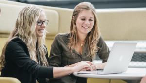 Zwei Studierende vor einem Laptop in der Aula