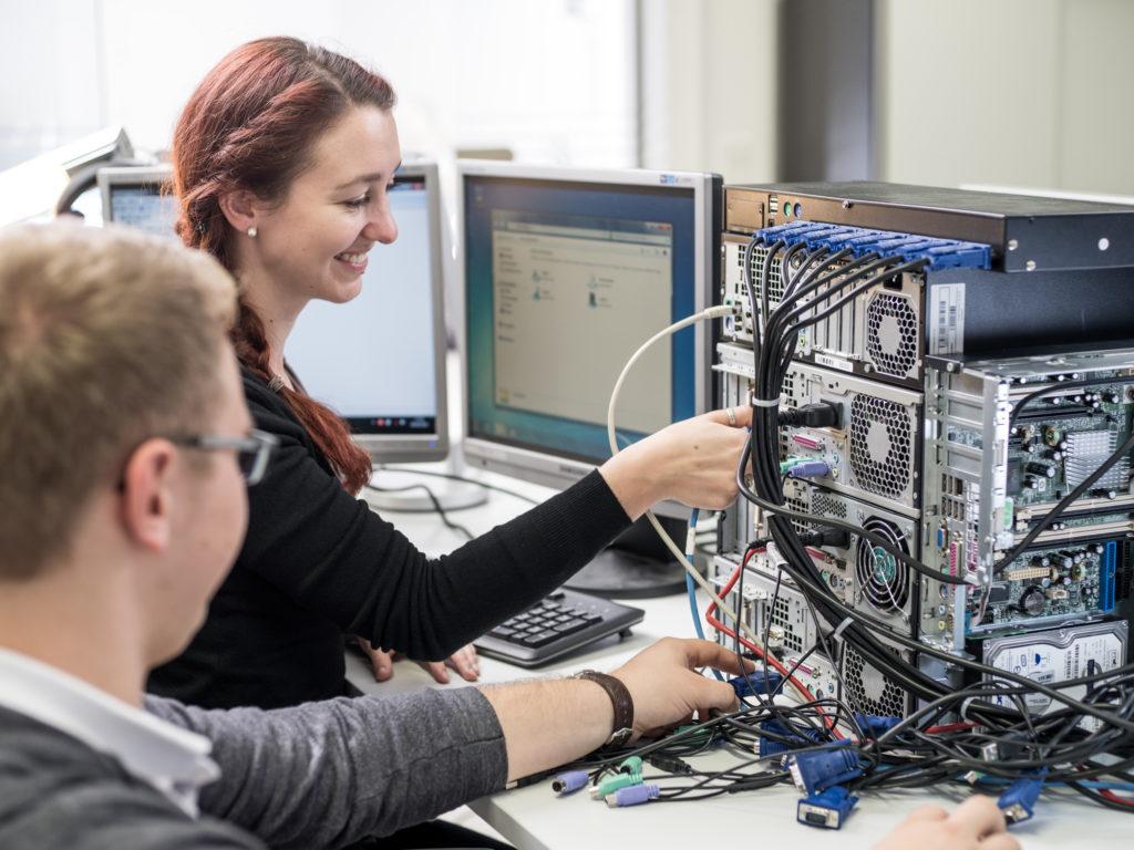 Zwei Studierende arbeiten an der Installation einer PC Anlage