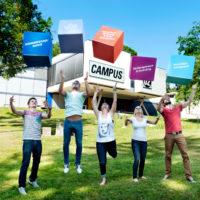 Fünf Studierende mit Würfeln vor dem FH Gebäude