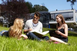 Studierende im Rasen vor dem FH Gebäude